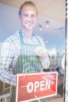 Waiter holding open signboard