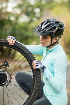Fit woman repairing bicycle tyre