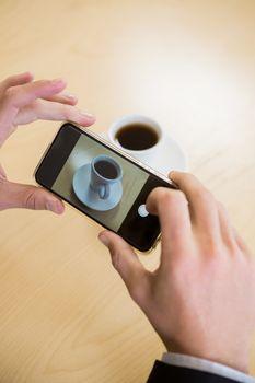 Man taking photograph of coffee