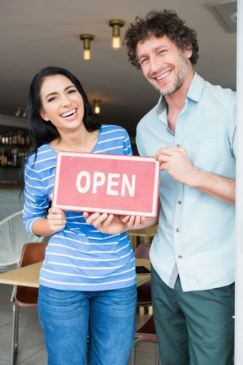 Couple holding open signboard
