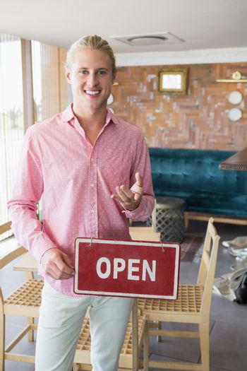 Restaurant manager holding open signboard