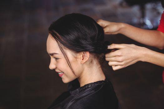 Female hairdresser styling customers hair