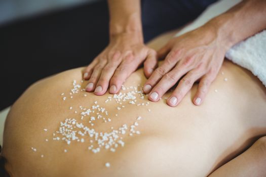 Woman receiving salt scrub therapy from physiotherapist