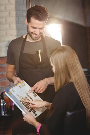 Woman selecting a hair color with stylist