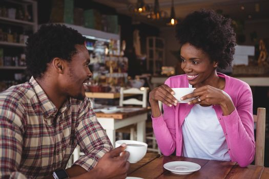 Young couple interacting with each other in cafeteria