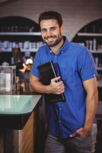 Portrait of smiling male hairdresser holding a diary at the hair salon