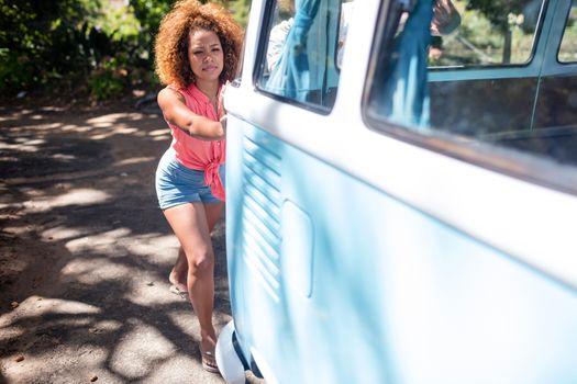 Woman pushing a campervan