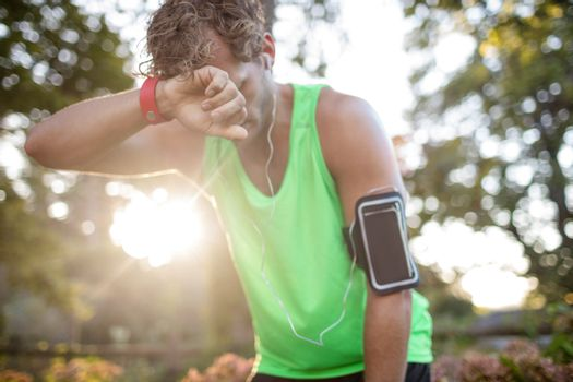 Tired man taking deep breath while jogging