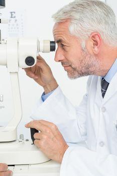 Senior optician in examination room