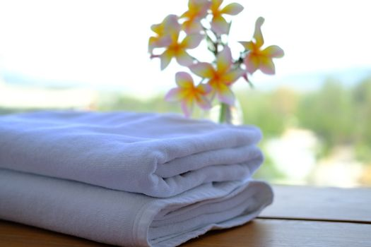 Close up of Stack of towels with fresh Plumeria flowers decor in a hotel room.