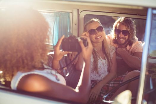 Woman taking photograph of friends in campervan on a sunny day