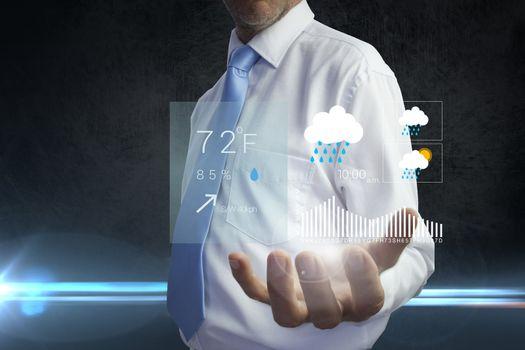Businessman holding a weather forecast hologram against black background