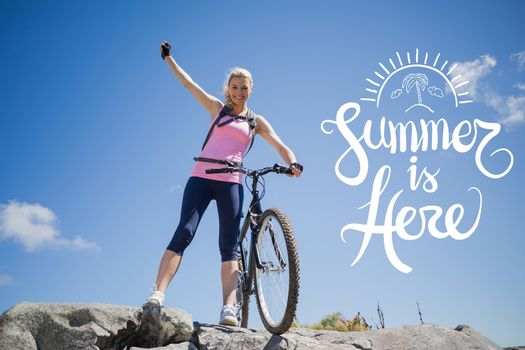 Cyclist standing on a mountain with arm up during summer time