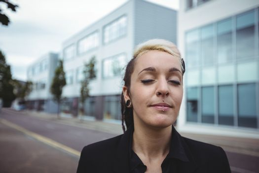Businesswoman standing with eyes closed