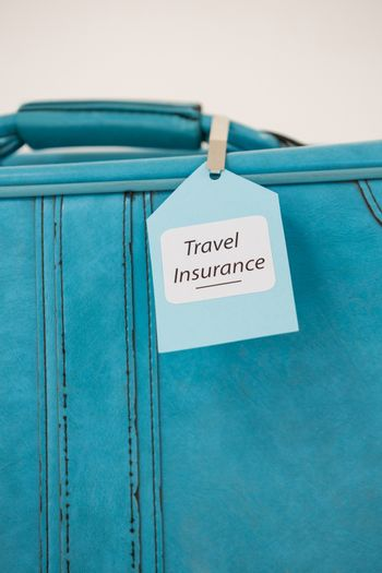 Close-up of travel insurance label tied to a suitcase