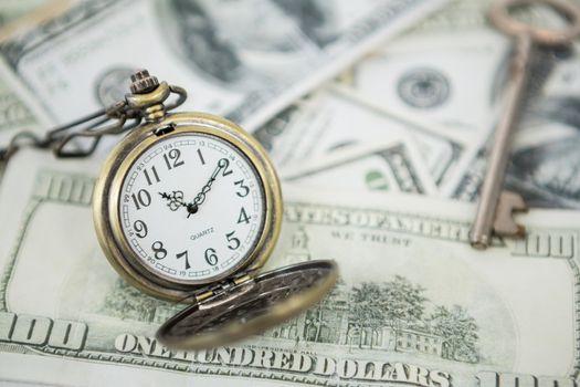 Pocket clock on one hundred dollar bills