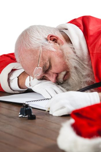 Santa claus sleeping at desk while writing a letter with a quill