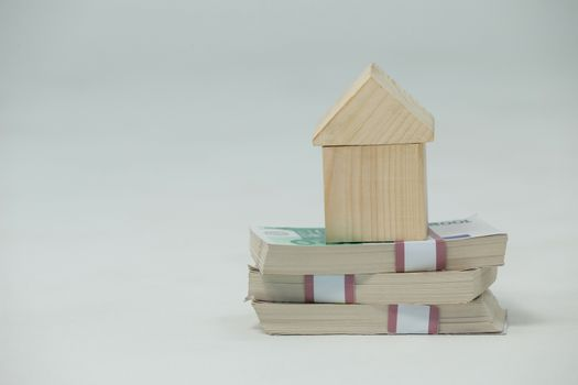 Model house on a pile of money on white background