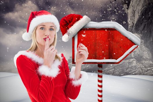 Female santa with finger on lips standing in snowfall