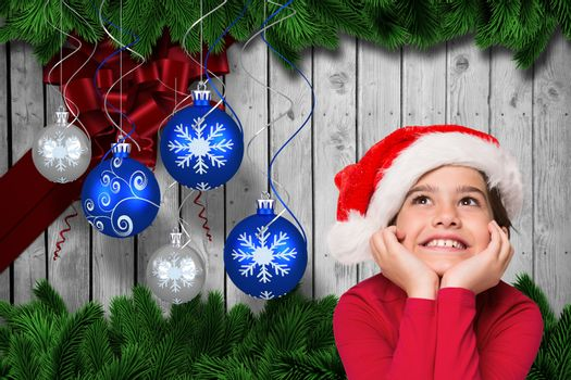 Girl in santa hat with hands on chin