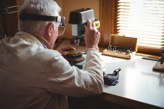 Horologist drilling a dial plate