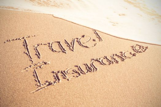 Travel Insurance text written on sand at beach