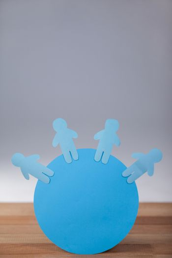 Conceptual image of blue and paper cut-out people on the circle