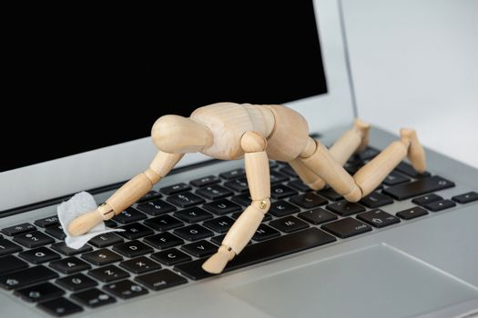 Wooden figurine cleaning the keypad of laptop with a cloth