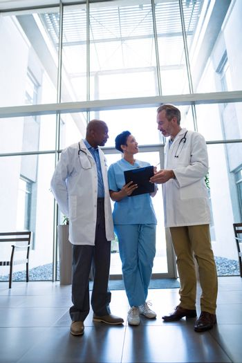 Surgeons and nurse discussing reports