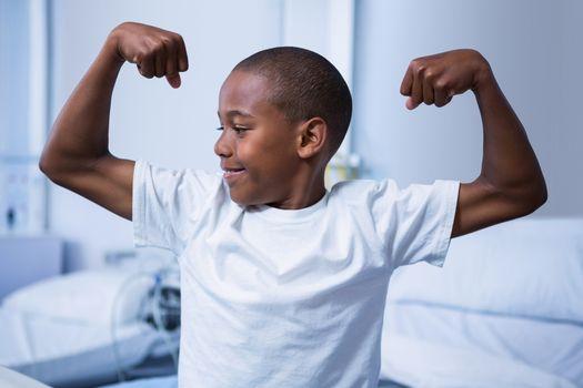 Boy flexing his muscles in ward