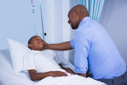 Male doctor consoling patient during visit in ward