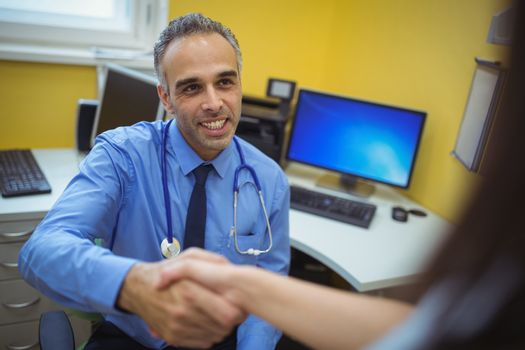 Doctor shaking hand with patient during visit