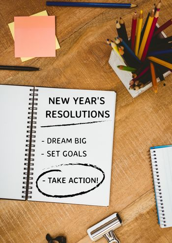 List of new year resolution goals with office supplies on wooden table