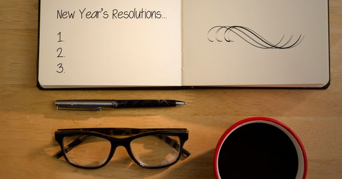 Blank list of new year resolutions in book with spectacles, coffee mug and pen on table