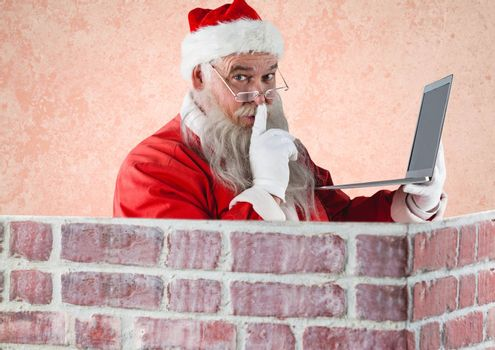 Portrait of santa claus with finger on lips holding a laptop