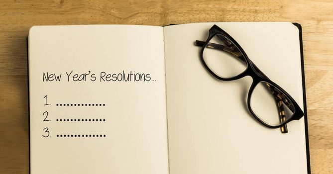 List of new year resolution goals in book with spectacles against wooden background