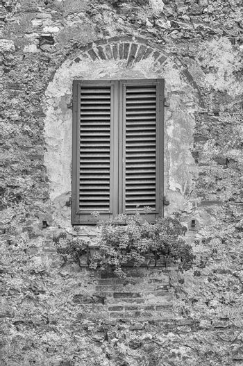 Scenic window in the medieval architecture of San Gimignano, iconic town in the province of Siena, and one of the most visited place in Tuscany, Italy