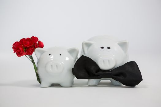 Two piggy bank with bunch of flower and bow bonding with each other