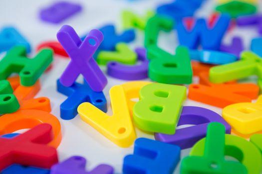 X alphabet standing between toy alphabet