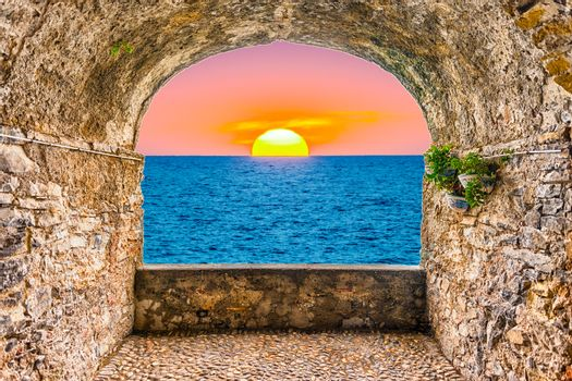 Scenic rock arch balcony overlooking a scenic sunset by the mediterranean sea, Italy