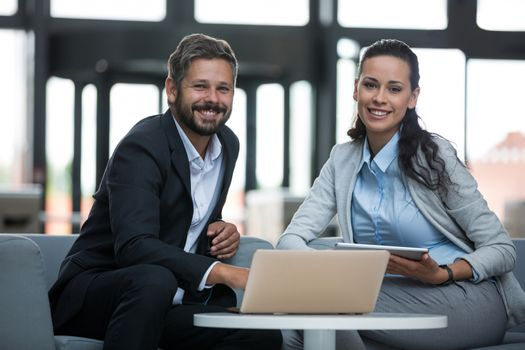 Happy businesspeople sitting with laptop