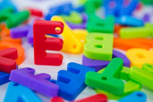 E alphabet standing between toy alphabet