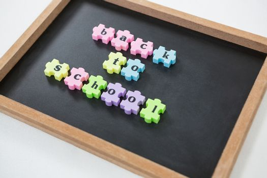 Close-up of back to school puzzle on slate