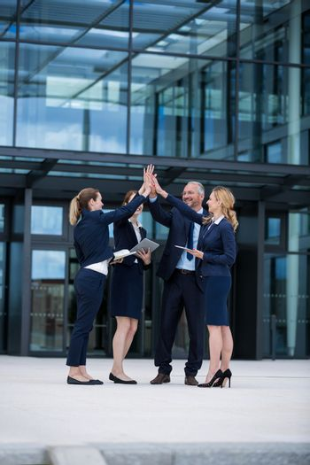 Happy businesspeople giving high five to each other