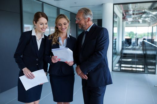 Happy businesspeople discussing over a report