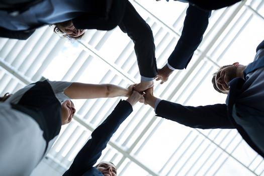 Group of happy businesspeople giving high five to each other