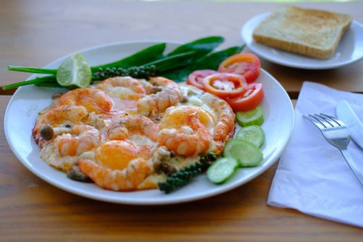 Close up of Fried eggs with prawns decorate fresh vegetables and toast, asian style food background