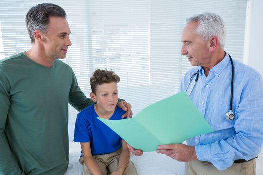 Doctor showing medical report to patient and his parent