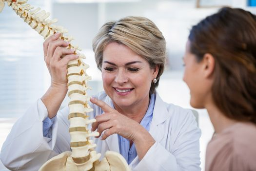 Doctor explaining anatomical spine to patient