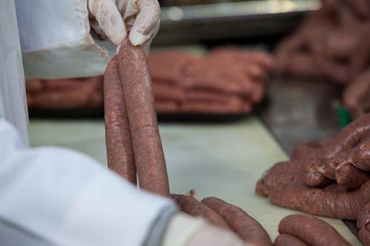 Butcher processing sausages